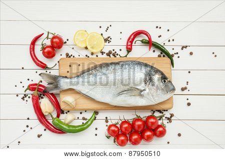 Fresh dorado fish with lemon on wooden cutting board
