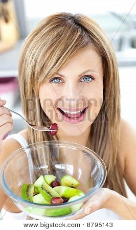 Jolly Woman Eating A Fruit Salad Smiling At The Camera In The Kitchen
