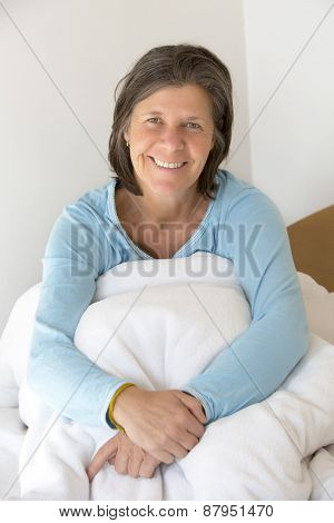 Smiling Woman Sitting In Bed