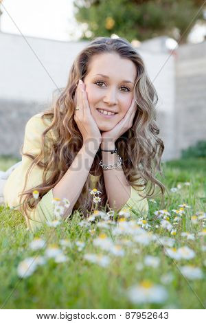 Blonde girl lying on the grass with many daisies around thinking