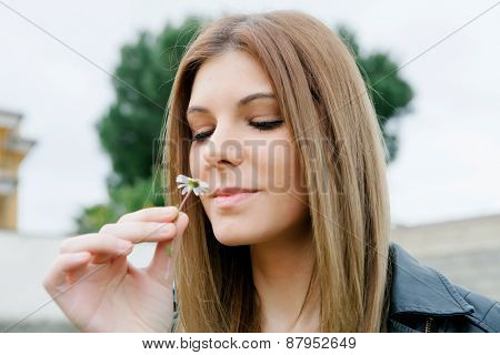 Pretty cool girl smelling a little daisy