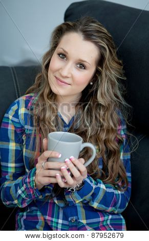 Attractive young girl sitting on the sofa drinking tea