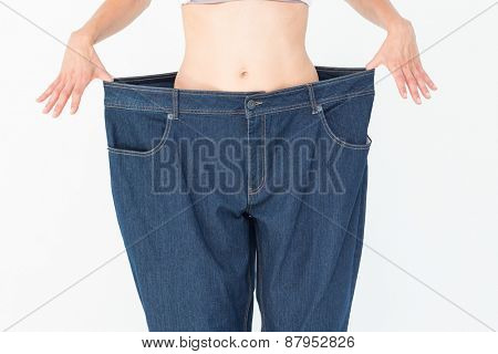 Woman wearing too large pants on white background