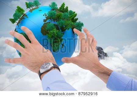 Businessman holding something with his hands against mountain peak through the clouds