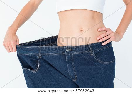 Slim woman wearing too big jeans on white background