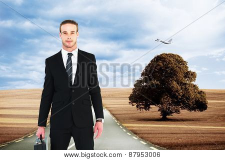Serious businessman standing and holding briefcase against road leading out to the horizon