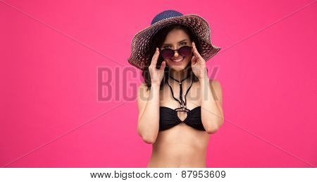 Smiling woman in swimsuit with hat and sunglasses over pink background