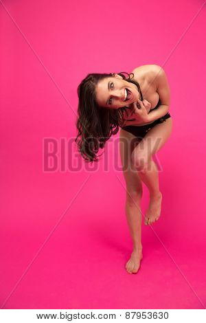 Funny young woman posing in bikini over pink background. And looking at camera