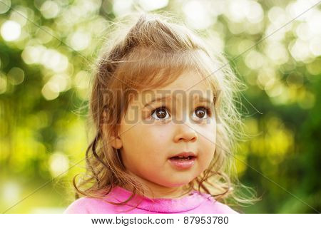 Cute little girl looking with interest in summer sunset