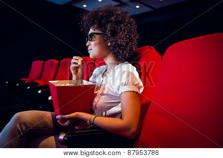 Young woman watching a 3d film and eating pop corn at the cinema