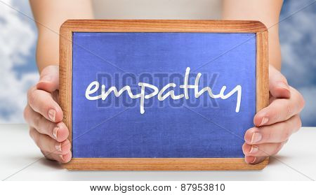 The word empathy and hands showing chalkboard against bright blue sky with clouds