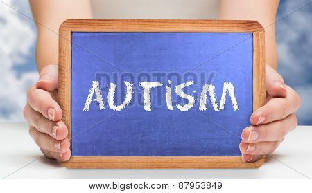 The word autism and hands showing chalkboard against bright blue sky with clouds