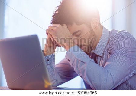 Businessman using laptop at desk shot in studio