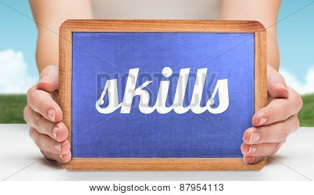 The word skills and hands showing chalkboard against field and sky