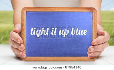 The word light it up blue and hands showing chalkboard against green meadow