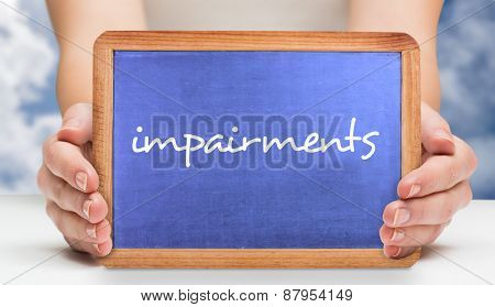 The word impairments and hands showing chalkboard against bright blue sky with clouds