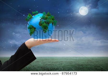 Hand presenting against green field at night