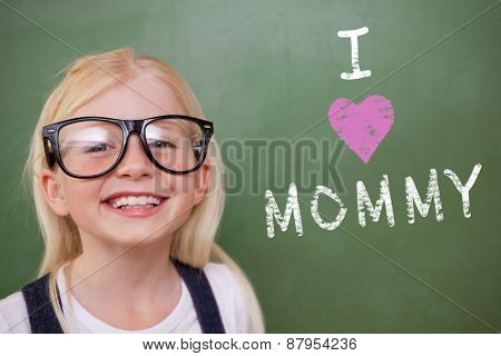 Cute pupil smiling against green chalkboard