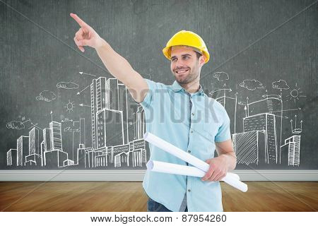 Male architect with blueprints pointing away against room with wooden floor