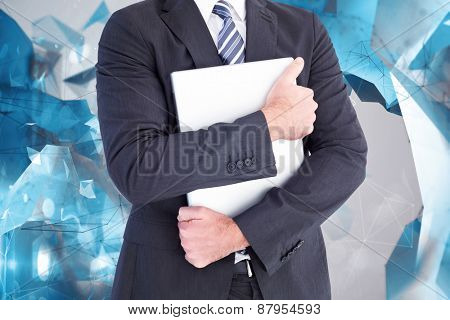 Businessman holding his laptop tightly against angular design