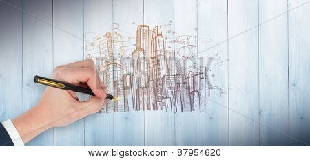 Hand holding a fountain pen against pale grey wooden planks