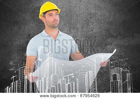 Thoughtful male architect holding blueprint against blackboard