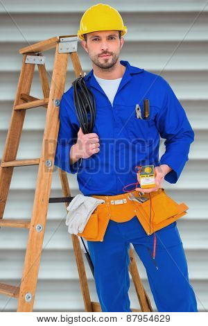 Electrician holding cables and multimeter against grey shutters