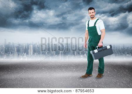 Repairman holding toolbox against road