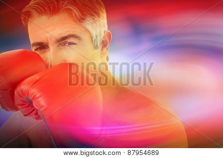 Fit man punching with boxing gloves against purple sky