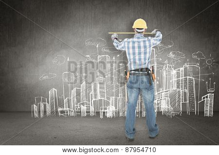 Rear view of construction worker using measure tape against hand drawn city plan