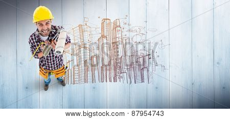 Frustrated handyman holding various tools against pale grey wooden planks