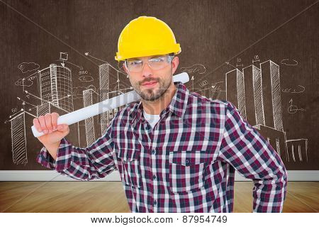 Handyman holding rolled up blueprint against room with wooden floor