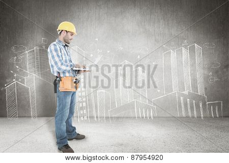 Full length of repairman using laptop against hand drawn city plan