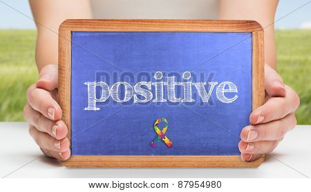 The word positive and hands showing chalkboard against green meadow