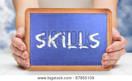 The word skills and hands showing chalkboard against bright blue sky with clouds