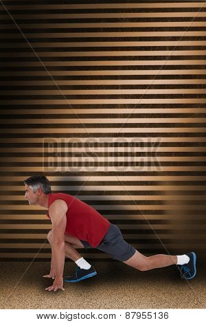 Fit man stretching his legs against dark grey room