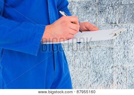 Male mechanic writing on clipboard against grey