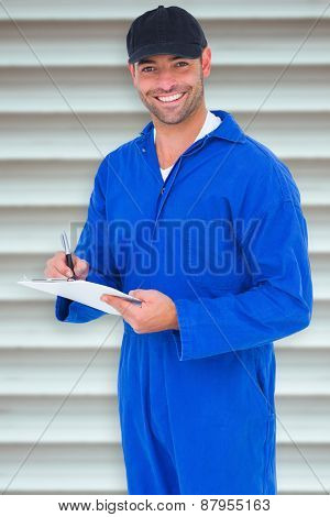 Handyman in blue overall writing on clipboard against grey shutters