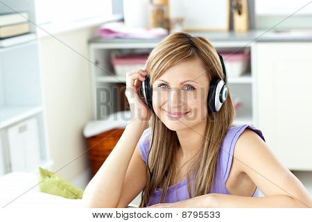 Joyful Caucasian Woman Listening To Music With Headphones In The Kitchen