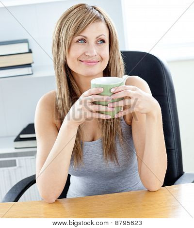 Relaxed Businesswoman Holding A Cup Of Coffee In Her Office