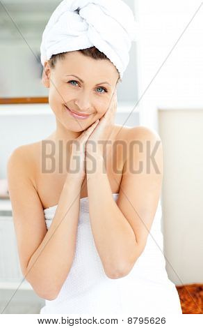 Attractive Young Woman With A Towel Putting Cream On Her Face In The Bathroom
