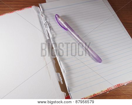Opened And Torn Notebook With Ballpoint Blue Ink On Wood Background