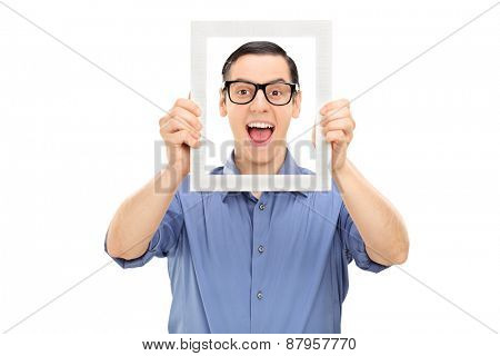 An excited young guy with glasses, posing behind a white picture frame isolated on white background