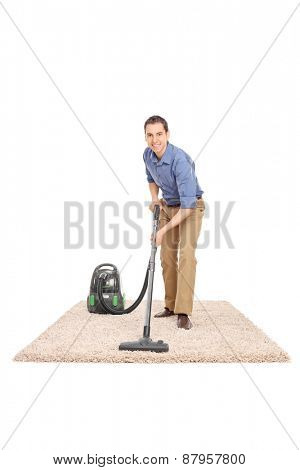 Full length portrait of a cheerful young man cleaning with a vacuum cleaner and looking at the camera isolated on white background
