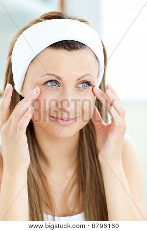 Cute Young Woman Putting Cream On Her Face In The Bathroom