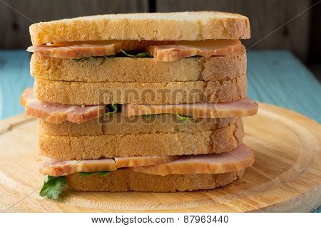 Three Sandwiches With Smoked Pork On Wooden Plate