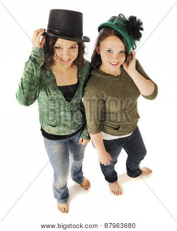 Overhead view of two barefoot young teen girl looking up at the viewer as they model old time hats.  On a white background.