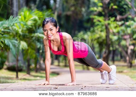 Proud and successful woman doing sport push-up in tropical Asian park, looking in camera during her exercise
