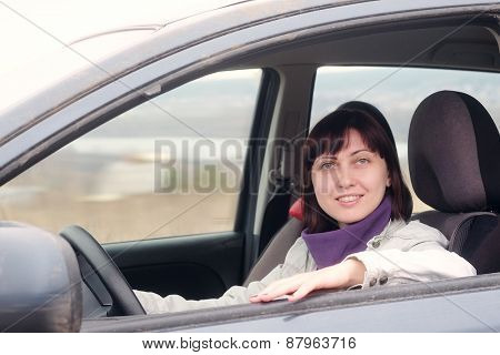 Happy woman sitting behind the wheel of a car smiling and looking at camera