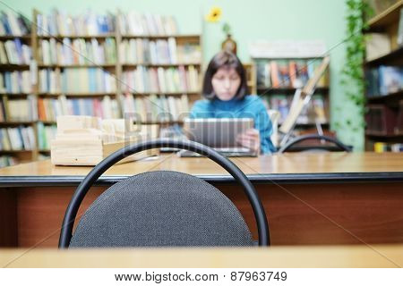 Librarian working in the library. In the foreground a chair back